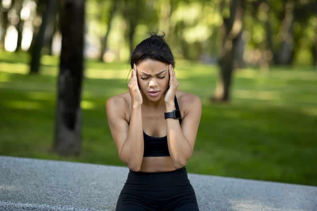 Black woman jogger having headache during training at park