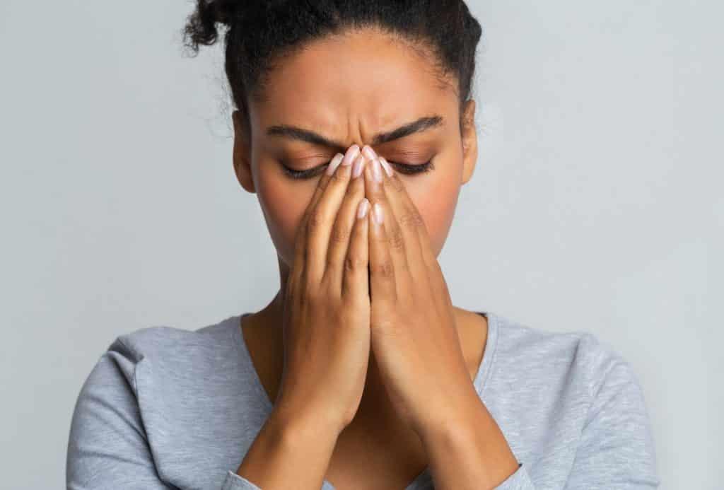 Young black woman touching her nose bridge